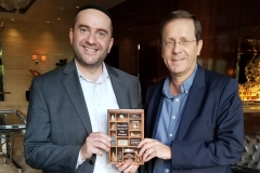 "Jewish Agency Chairman Isaac ""Buji"" Herzog receives his copy of Rabbi Dunner's book Mavericks, Mystics & False Messiahs, at his hotel in Los Angeles, December 2, 2018"